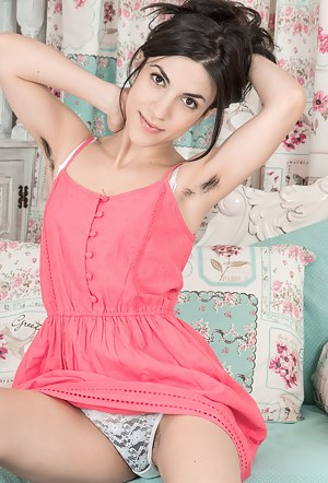 Luna O stands in her pink dress looking extra lovely. She takes off the dress and lingerie and is naked across her chair. She has hairy pits and a full hairy pussy, that she loves to show off and get off.
